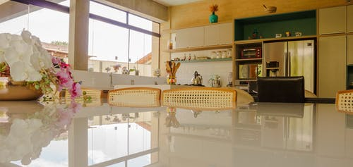 Glass table decorated with flower arrangement and wooden chairs located in comfortable stylish kitchen with white furniture