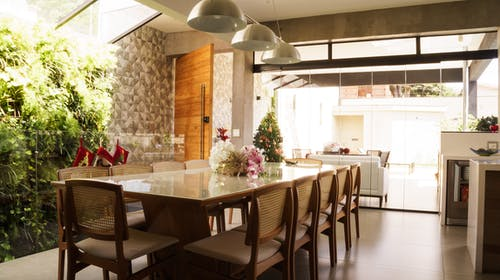 Interior of cozy spacious kitchen with glass table and comfortable seats decorated for Christmas celebration with small tree illumination and stockings