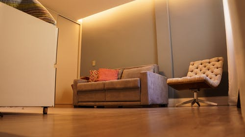From below of contemporary living room with comfortable couch and chair on parquet floor under light ceiling