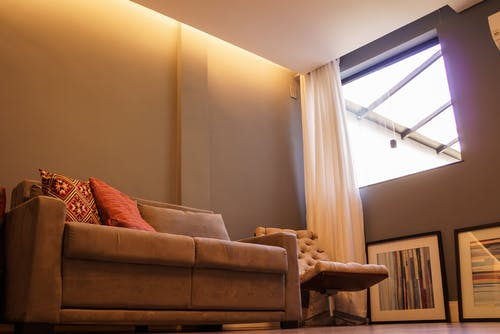 Interior of cozy apartment with comfortable couch and cushions with stretch ceiling and light