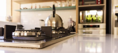 Selective focus of modern gas stove against kettle oven and mixer placed in cozy kitchen