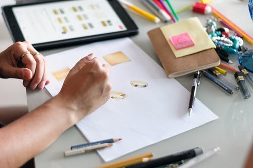 Woman drawing sketches of accessories on paper