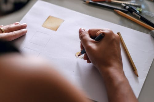 Woman drawing sketch on paper in workshop