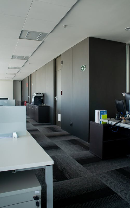 Interior design of workspace equipped with tables and monitors with large cabinets at daytime