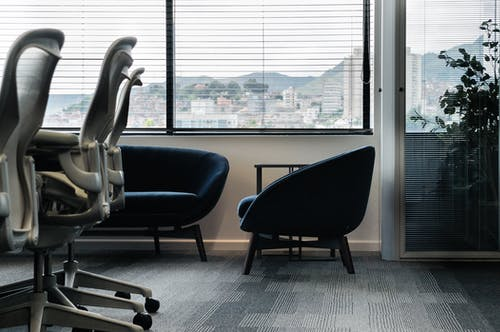 Comfortable soft furniture and modern office chairs in empty conference room with blinds on windows