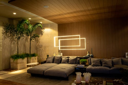 Modern living room interior with cozy sofas and shiny lamps