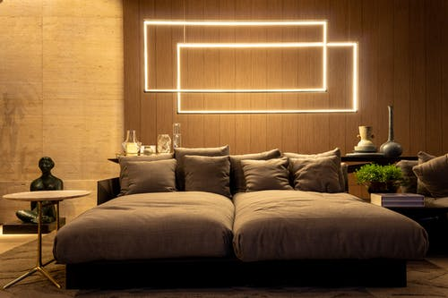 Comfortable sofa bed with cozy cushions placed in contemporary living room under creative geometric wall lamps