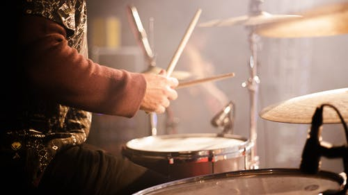 Side view crop anonymous male musician playing drums during live concert on concert stage