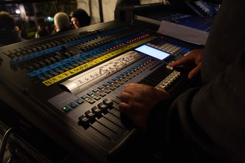 Crop anonymous male sound director adjusting faders on modern mixer board during live concert