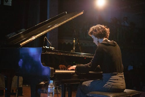 Female pianist playing piano on stage during concert