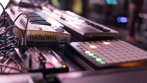 Sound designing instruments including electric keyboards and launchpad placed on stage during live concert or in studio