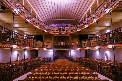 Interior design of modern small theater hall including mezzanine and balconies with wooden chairs