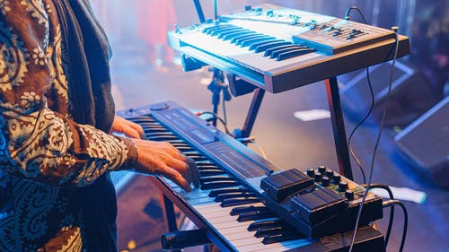 Crop unrecognizable musician playing synthesizer at concert