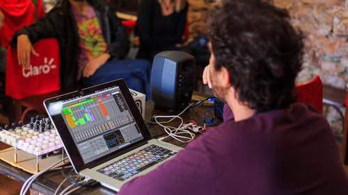 Unrecognizable sound director sitting at table with laptop and mixer