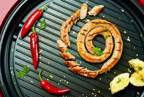 Overhead composition of appetizing grilled sausage cut on grill pan and garnished with aromatic chili peppers and lemon slices