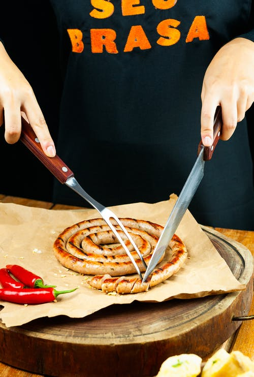 Crop unrecognizable person in casual shirt cutting palatable grilled sausage on parchment paper