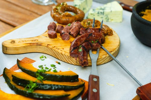 Composition of appetizing cut sausage served on wooden board with boiled pumpkin and blue cheese