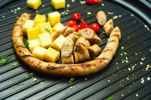 Slices of sausage and cheese on grill pan
