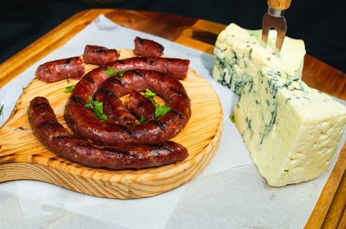 Fork in blue cheese and long thin spiral grilled sausage on cutting board in daytime