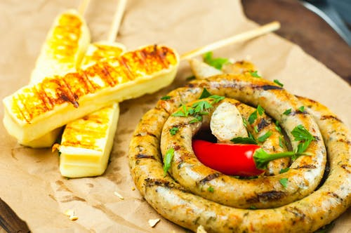 Vibrant red pepper on long thick grilled sausage covered with green parsley next to cheese skewers on parchment paper