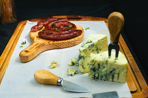 Fork in cheese and sausage on cutting board in bright room