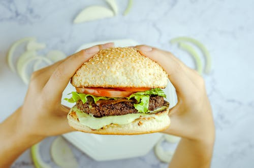 Anonymous person eating hamburger with cutlet and fresh vegetables