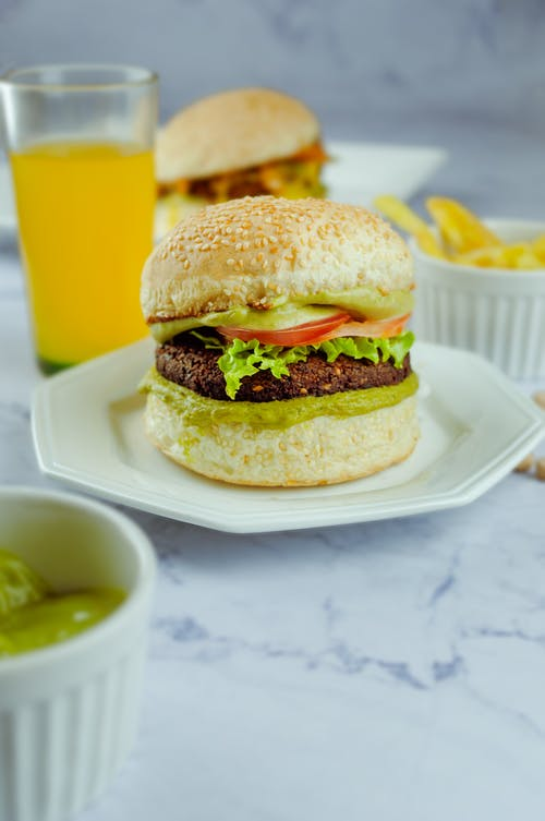 Appetizing hamburger with cutlery and lettuce between buns surrounded by orange juice and plate with sauce