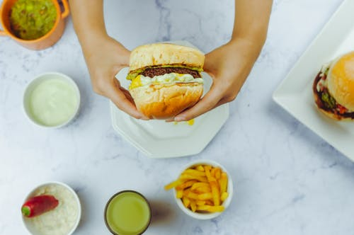 Crop person holding fresh burger over table