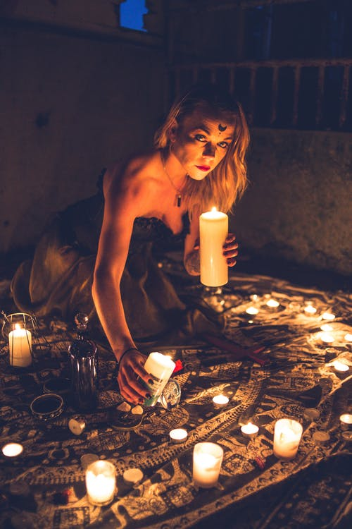 Mysterious woman among candles during dark ritual