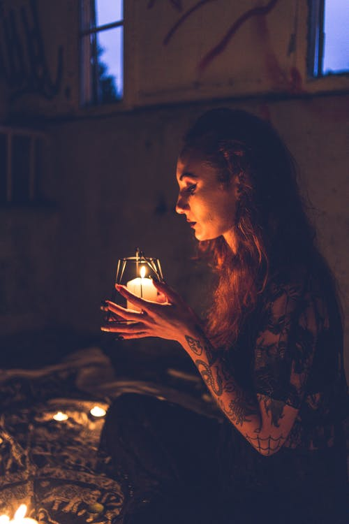 Tattooed woman praying with candle in darkness