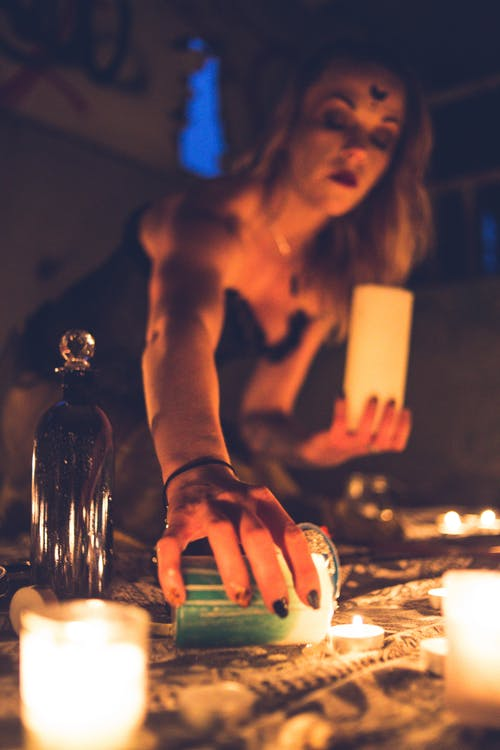 Witch lighting candles for occult ritual