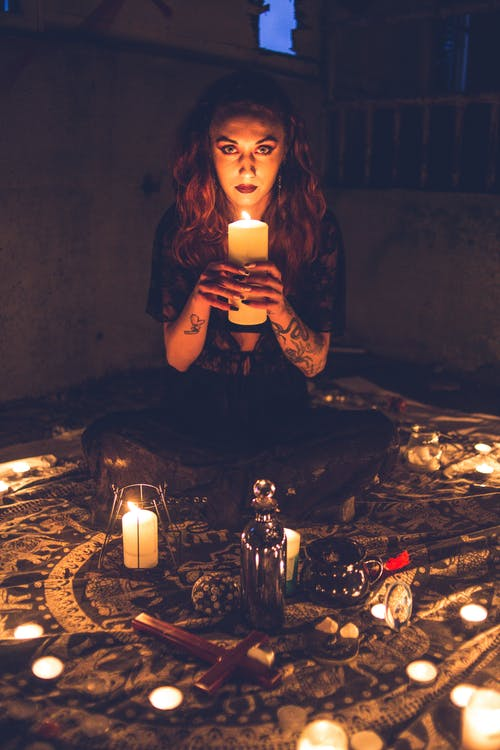 Spooky witch with candles in darkness