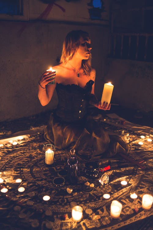 Dark witch worshiping among candles