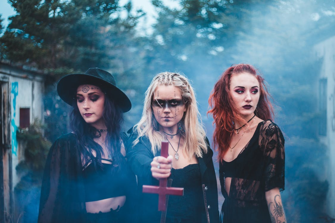 Spooky females in dark clothes with inverse cross standing together in blue colored smoke agains trees