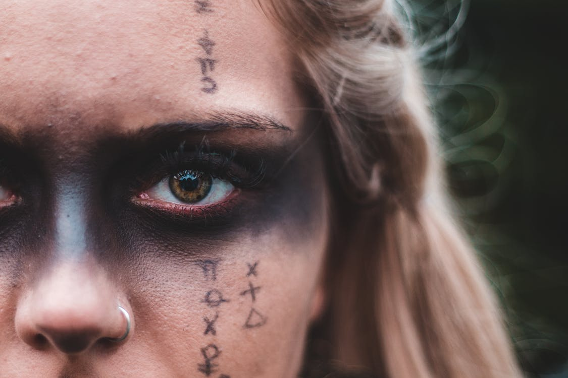 Closeup crop blond with black painted mask on eyes and symbols on skin looking at camera