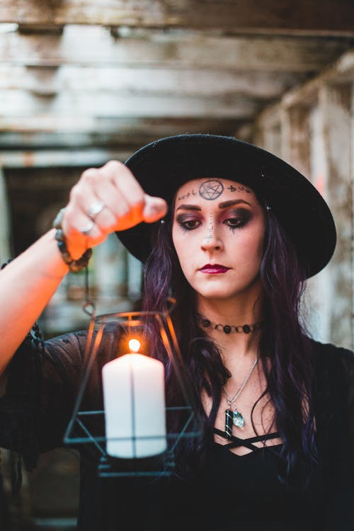 Woman in hat holding burning candle