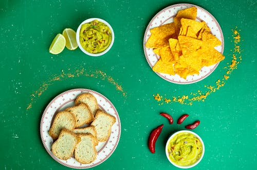 Flat lay of nachos near guacamole sauces and sliced white bread on plates