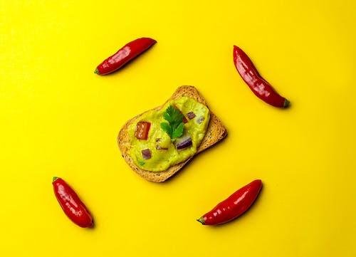 Delicious guacamole on bread near pepper
