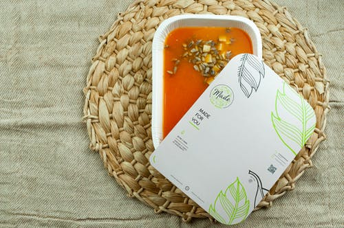 Fresh soup in container on table