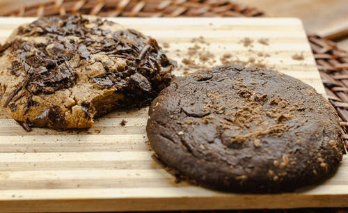 Closeup of baked cookies with chocolate on wooden board on table at home