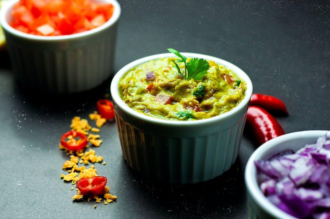 Delicious Mexican guacamole in ceramic bowl