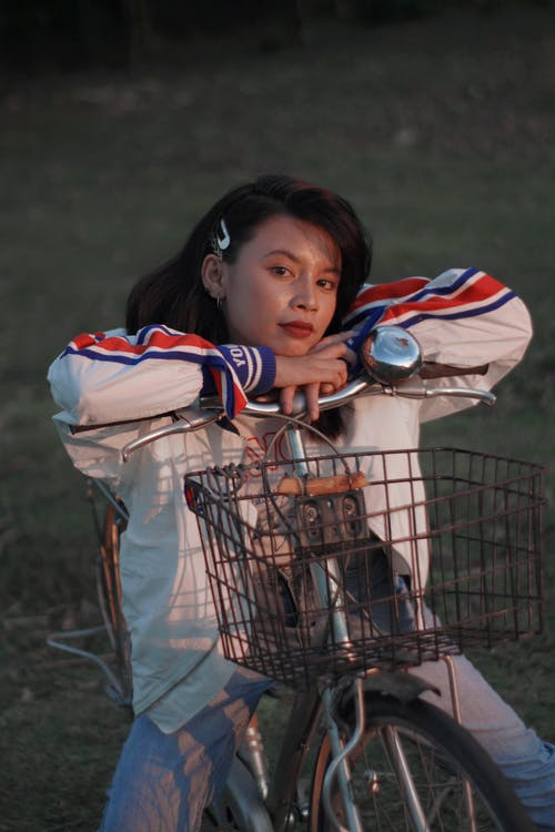 Girl in White and Red Jacket Holding a White and Blue Soccer Ball