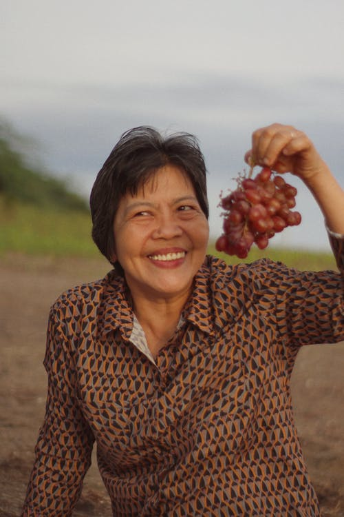 Close-Up Shot of a Happy Woman Holding Fresh Grapes