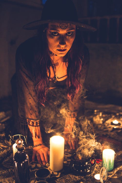 Spooky sorceress among candles in dark