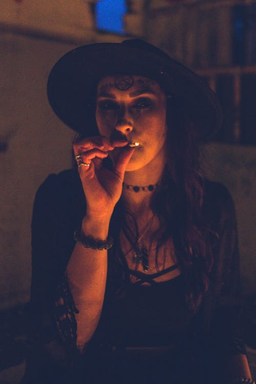 Female in black clothes and hat standing in darkness with soft light and smoking while looking at camera