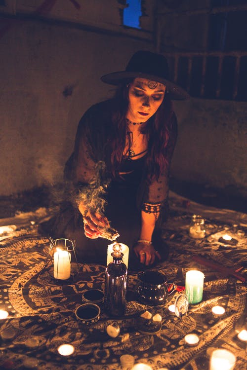 Sorceress burning sage incense with candle