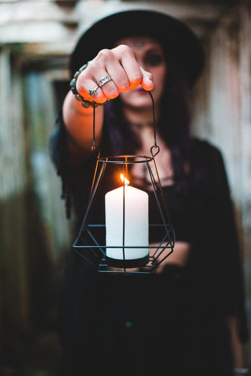 Dark witch holding lantern with candle