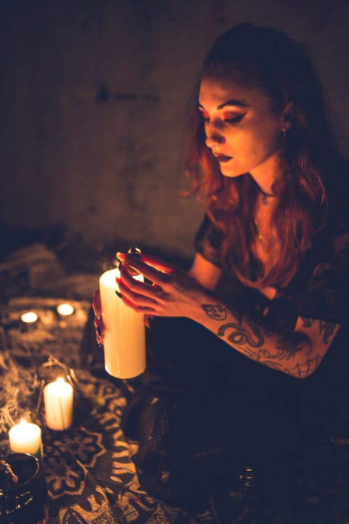 Calm mysterious woman with tattooed arm holding bright burning candle in dark