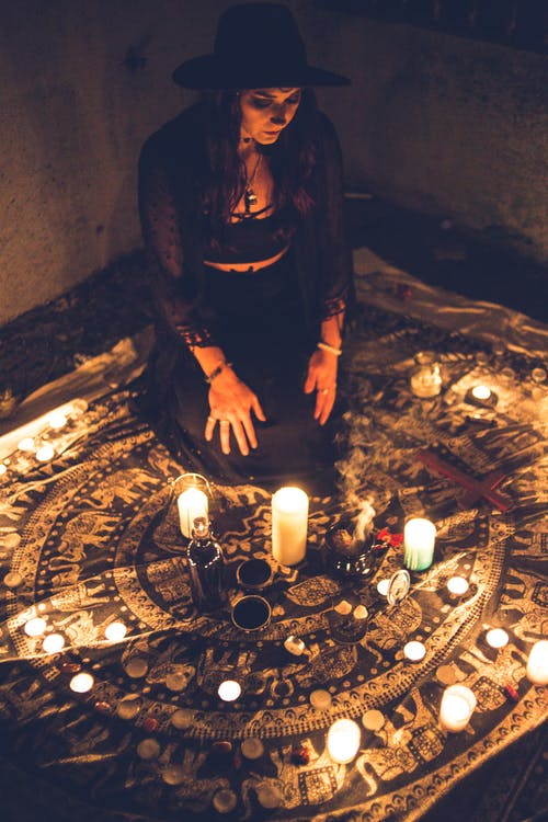 Sorceress among candles in darkness