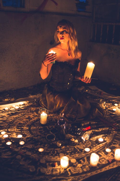 Enchantress with candles on carpet in night